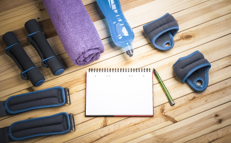 isotonic: Sport Equipment. Dumbbells,  Ankle Weights, Wrist Weights, Towel, Isotonic Drink And Notebook To Workout Plan On Table. Sport Fitness Background Stock Photo