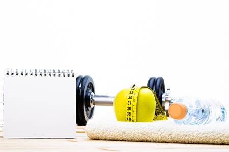 weight loss plan: Sport Equipment. Dumbbells,  Towel, Apple, Tape Measure, Bottle Of Water And Notebook To Workout Plan On Wooden Table With White Background. Stock Photo