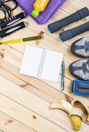 saltar la cuerda: Sport Shoes, Dumbbells, Ankle Weights, Jump Rope, Towel, Tape Measure, Banana, Orange Juice, Notepad To Workout Plan On Wooden Floor. Sport Fitness Background