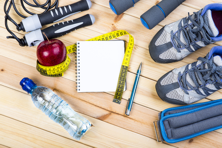 jump rope: Sport Shoes, Dumbbells, Jump Rope, Ankle Weights, Tape Measure, Apple, Bottle Of Water, Notepad To Workout Plan On Wooden Floor. Sport Fitness Background