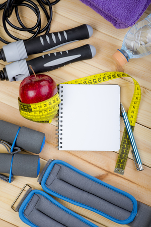 saltar la cuerda: Dumbbells, Jump Rope, Towel, Ankle Weights, Tape Measure, Apple, Bottle Of Water, Notepad To Workout Plan On Wooden Floor. Sport Fitness Background