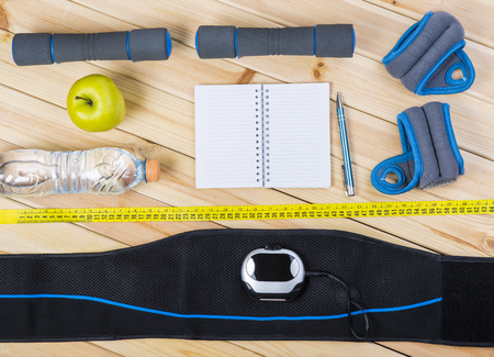 stimulation: Electrical Muscle Stimulation Belt, Dumbbells, Ankle Weights, Tape Measure, Apple, Bottle Of Water, Notepad To Workout Or Diet Plan On Wooden Floor. Sport Fitness Background.