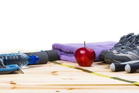 jump rope: Dumbbells, Jump Rope, Towel, Sport Shoes, Ankle Weights, Tape Measure, Apple And Bottle Of Water On Wooden Floor. Sport Fitness Background. Stock Photo
