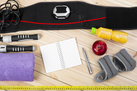 jump rope: Electrical Muscle Stimulation Belt, Jump Rope, Ankle Weights, Towel, Tape Measure, Apple, Bottle Of Juice, Notepad To Workout Or Diet Plan On Wooden Floor. Sport Fitness Background. Stock Photo