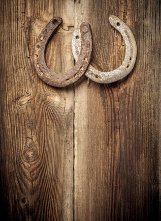 herradura: Dos oxidadas herraduras se cuelga en la pared de madera vieja del granero. Concepto suerte