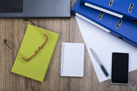 ring binders: Top View Of An Office Desk With Laptop, Ring Binders, Smartphone, Glasses, Calendar, Pen. Sheet Of Paper And Notepad. Stock Photo