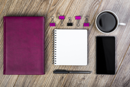 spiral notebook: Top View Of An Office Desk With Calendar, Spiral Notebook, Smart Phone, Coffee Cup, Pen And Paperclips.