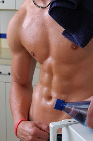Muscular man getting a bottle of water