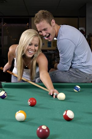 cue sticks: Couple playing pool