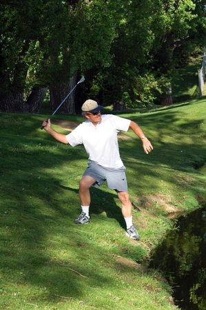 An angry golfer about to throw his club in the water trap