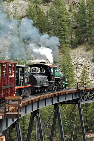 An old steam locomotove going over a bridge Stock Photo
