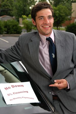 A car salesman pointing at a car Stock Photo