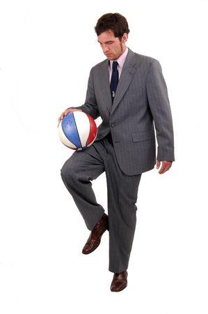 A businessman bouncing a basketball on his knee 免版税图像