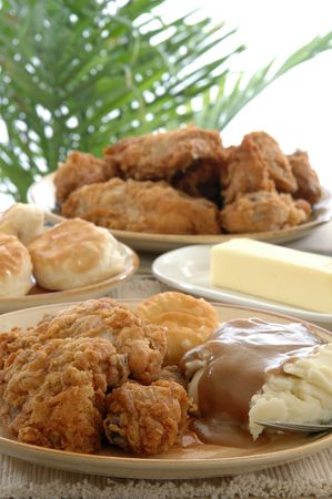 heaped: a table heaped with fried chicken, mashed potatoes and rolls