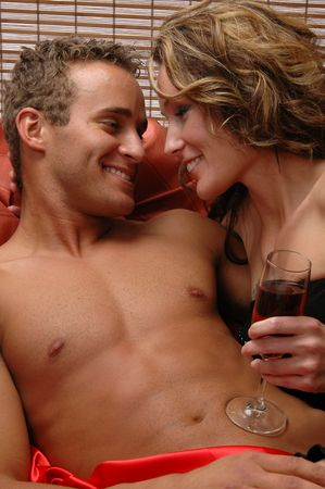 A loving couple sharing a glass of champagne in bed