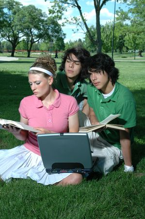Friends outdoors in the park studying for final exams photo