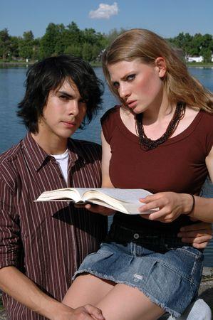 Una joven pareja leyendo un libro sobre la orilla de un lago  Foto de archivo - 1117396