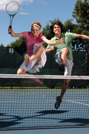A young couple jumps over the net with tennis rackets