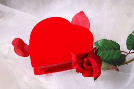 A heart shaped box of chocolates with a rose on white lace. Shallow DOF photo