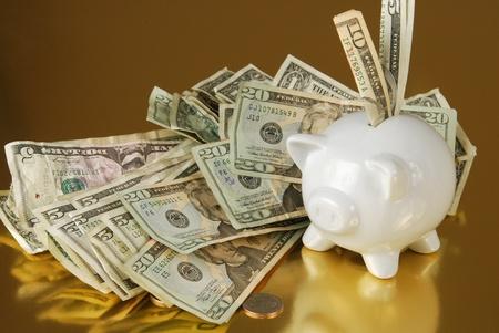 Een spaarvarken op goud vol met contanten Stockfoto