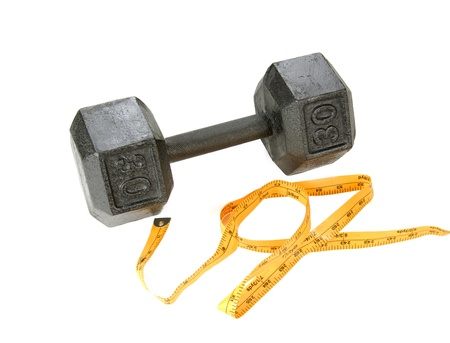 A tape measure sits by a set of dumbells