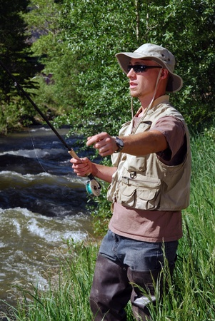 A fisherman casting his line in a stream