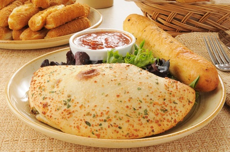 A plate with a calzone and a brread stick Imagens