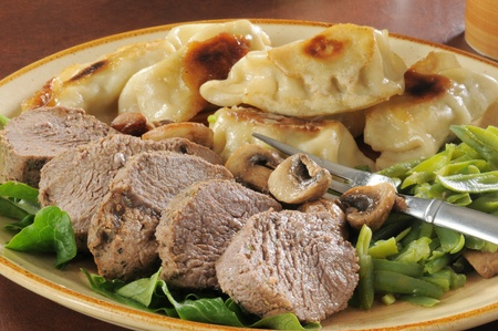 potstickers: A plate of roast beef and potstickers with green beans