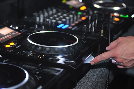 audio mixer: Close up of a DJ in a nightclub inserting a new disc into the sound system