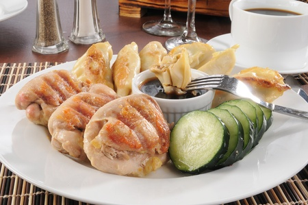 A plate of chicken with potstickers and sliced cucumber photo