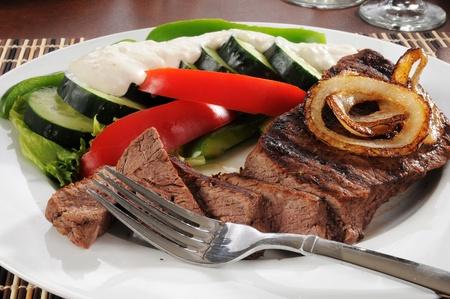 A sliced sirloin steak and fresh vegetables