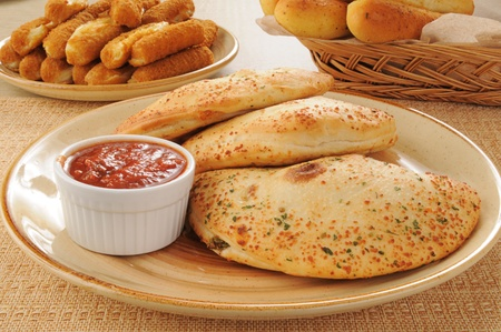 A plate of calzones with cheese and bread sticks