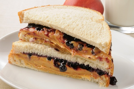 peanut butter and jelly sandwich: A peanut butter and strawberry jelly sandwich with an apple and milk