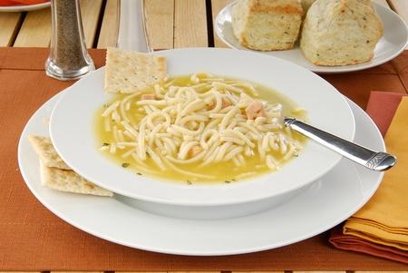 sopa de pollo: Un tazón de sopa de pollo con fideos y galletas de soda