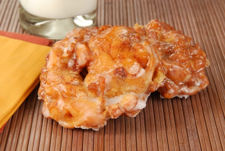 Two apple fritters on a placemat with milk