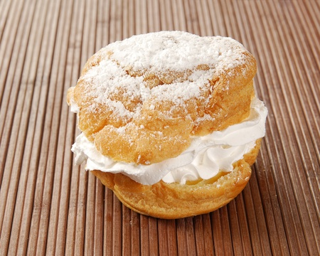 A single cream puff on a bamboo placemat