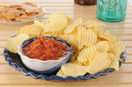 백그라운드에서 부서지기 쉬운 땅콩과 칩과 살사의 파티 접시 스톡 콘텐츠