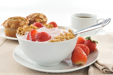A bowl of organic strawberry yogurt with granola and almond muffins Stock Photo - 12268103