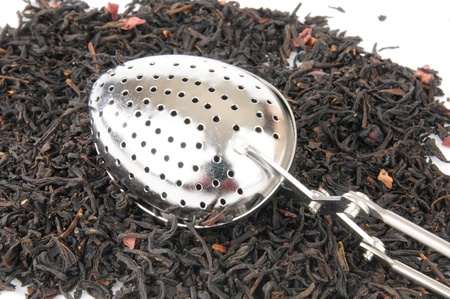 A silver tea infuser on top of a mound of black loose leaf tea Stock Photo - 12268120