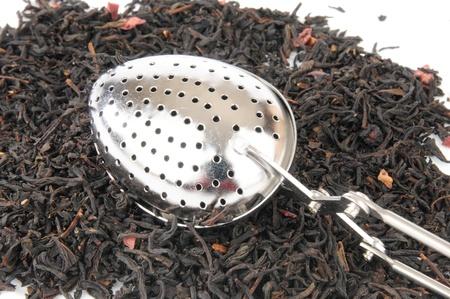 loose leaf: Una infusi�n de t� de plata en la parte superior de un mont�n de t� negro de hojas sueltas