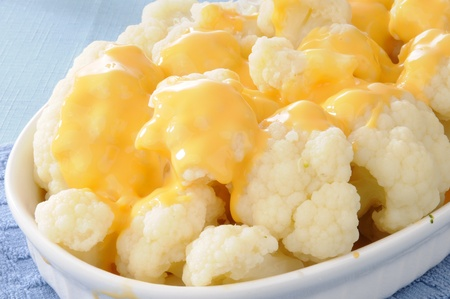 A casserole dish of steamed cauliflower and cheese sauce