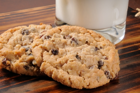 raisin: Two oatmeal raisin cookies with a glass of milk
