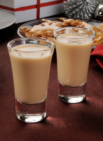 shooters: Two Irish Cream shooters in shot glasses on a table with Christmas gifts and decorations Stock Photo