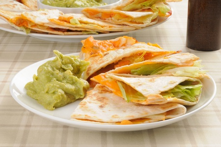 tex mex: A plate of cheddar cheese quesadillas with guacamole dip Stock Photo