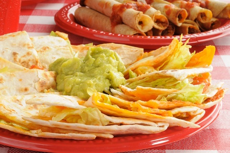 A plate of cheddar cheese quesadillas with guacamole and taquitos photo