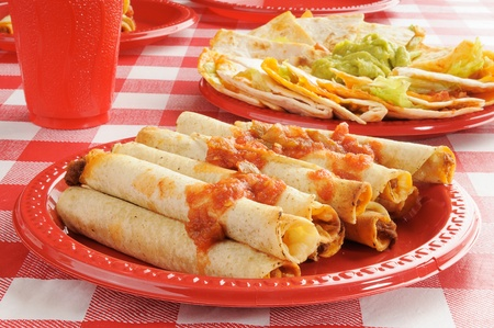 A plate of steak and cheese taquitos and quesadillas photo