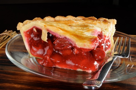 A rich fresh slice of cherry pie with a black background