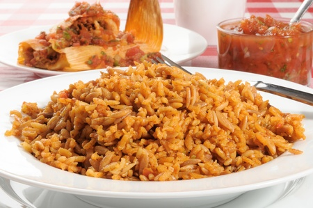 A bowl of Spanish or Mexican rice with tamales in the background