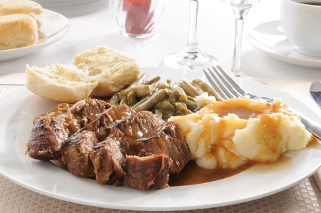 A plate of sliced beef pot roast with mashed potatoes and mushroom gravey