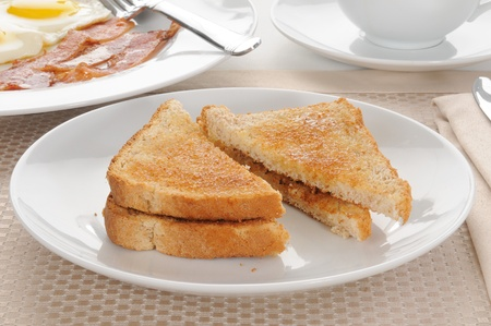 buttered: Buttered toast with a bacon and egg breakfast in the background
